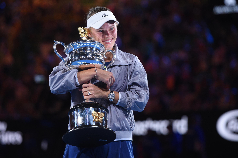 Caroline Wozniacki smiles and holds the 2018 Australian Open trophy