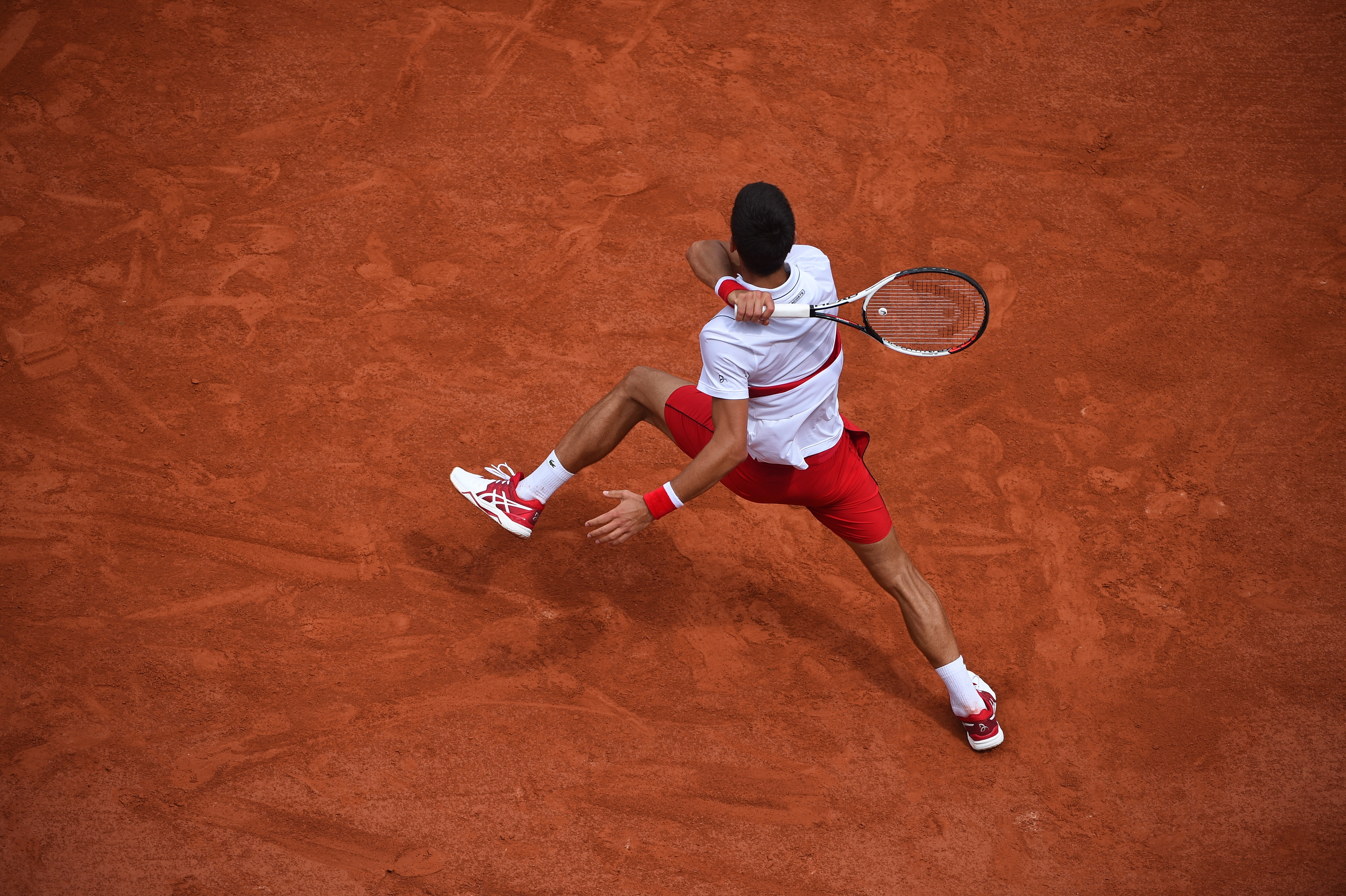 Dislocated Novak Djokovic hitting a forehand at Roland-Garros 2018