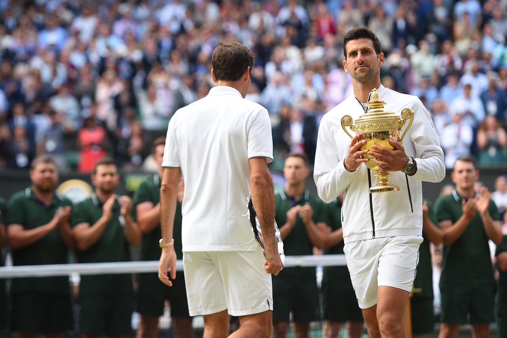 Novak Djokovic passing by Roger Federer with his trophy at Wimbledon 2019