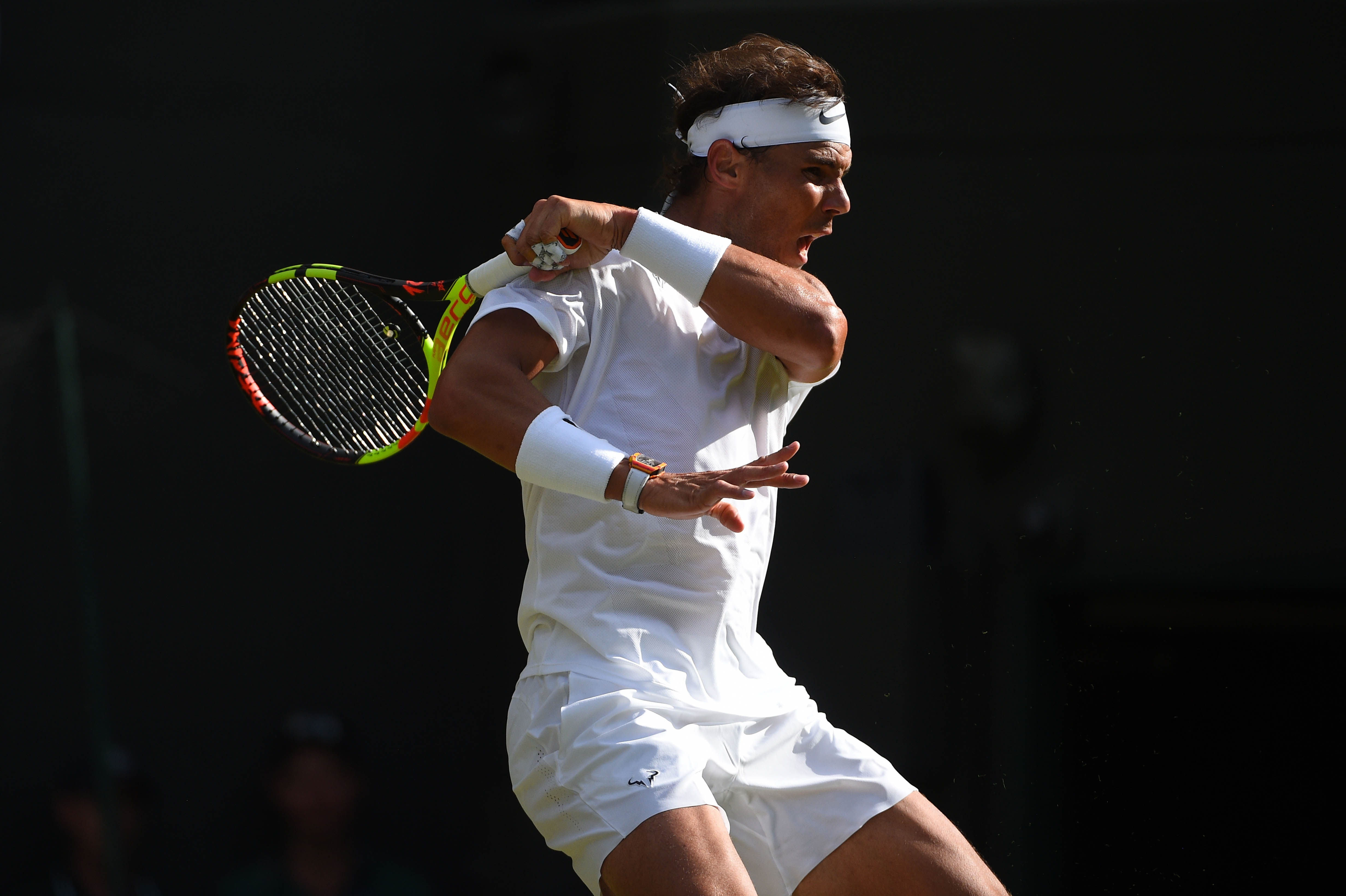 Rafael Nadal hitting a forehand in the light and shadow Wimbledon 2019