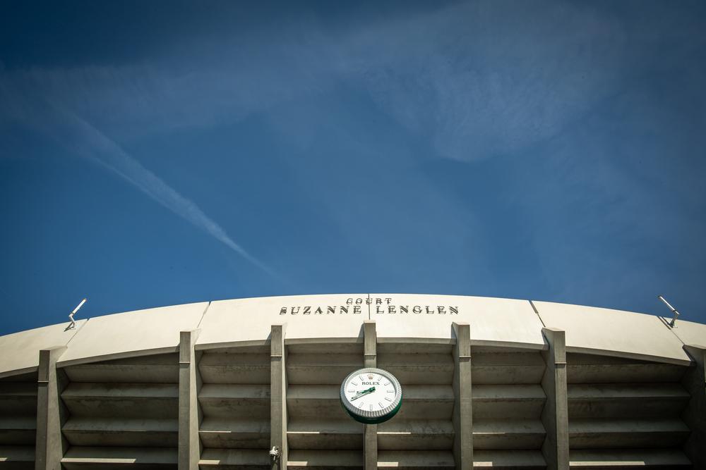 Ciel bleu sur le court Suzanne Lenglen et l'horloge Rolex avant le débutd e Roland-Garros 2019.