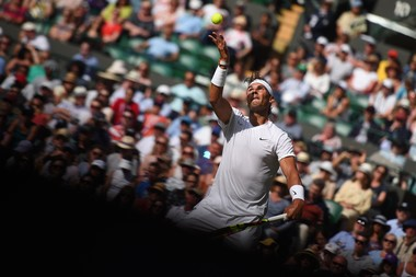 Rafael Nadal serving half in the light, half in the shadow Wimbledon 2019