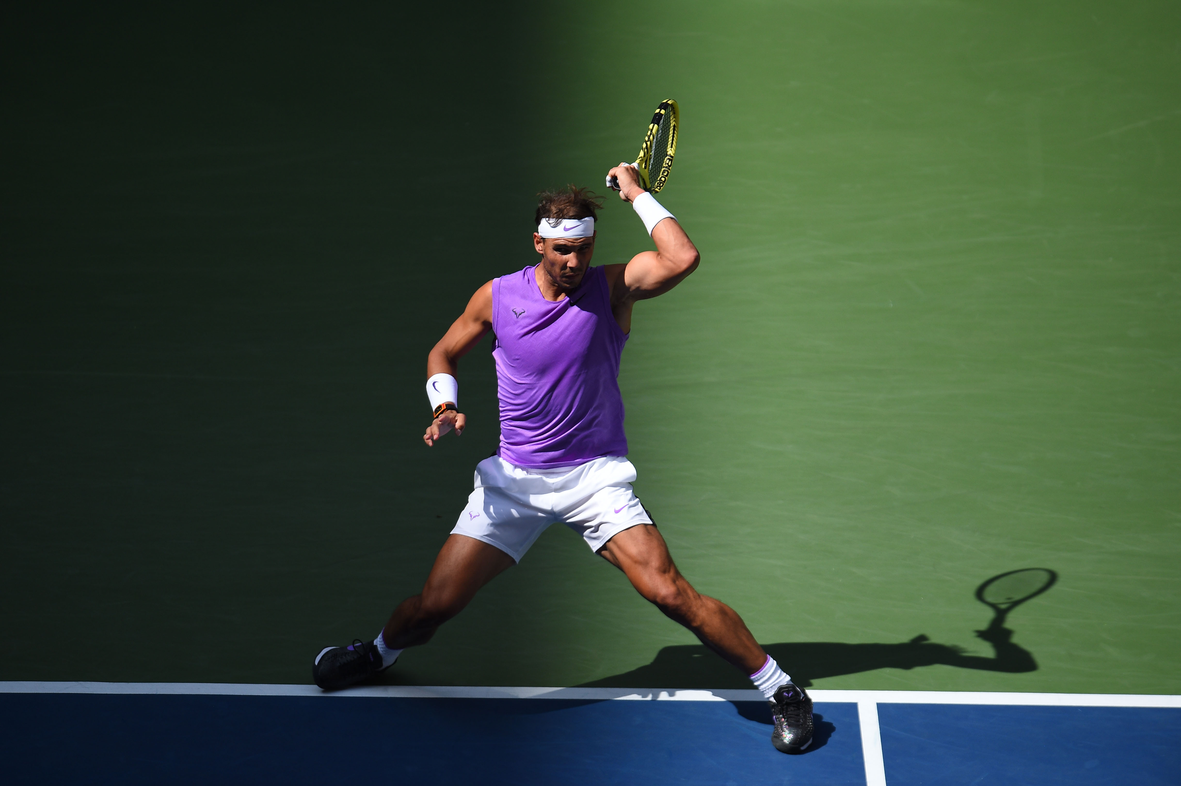 Rafael Nadal hitting a forhand in the light and shadow during hirs third round match at the 2019 US Open