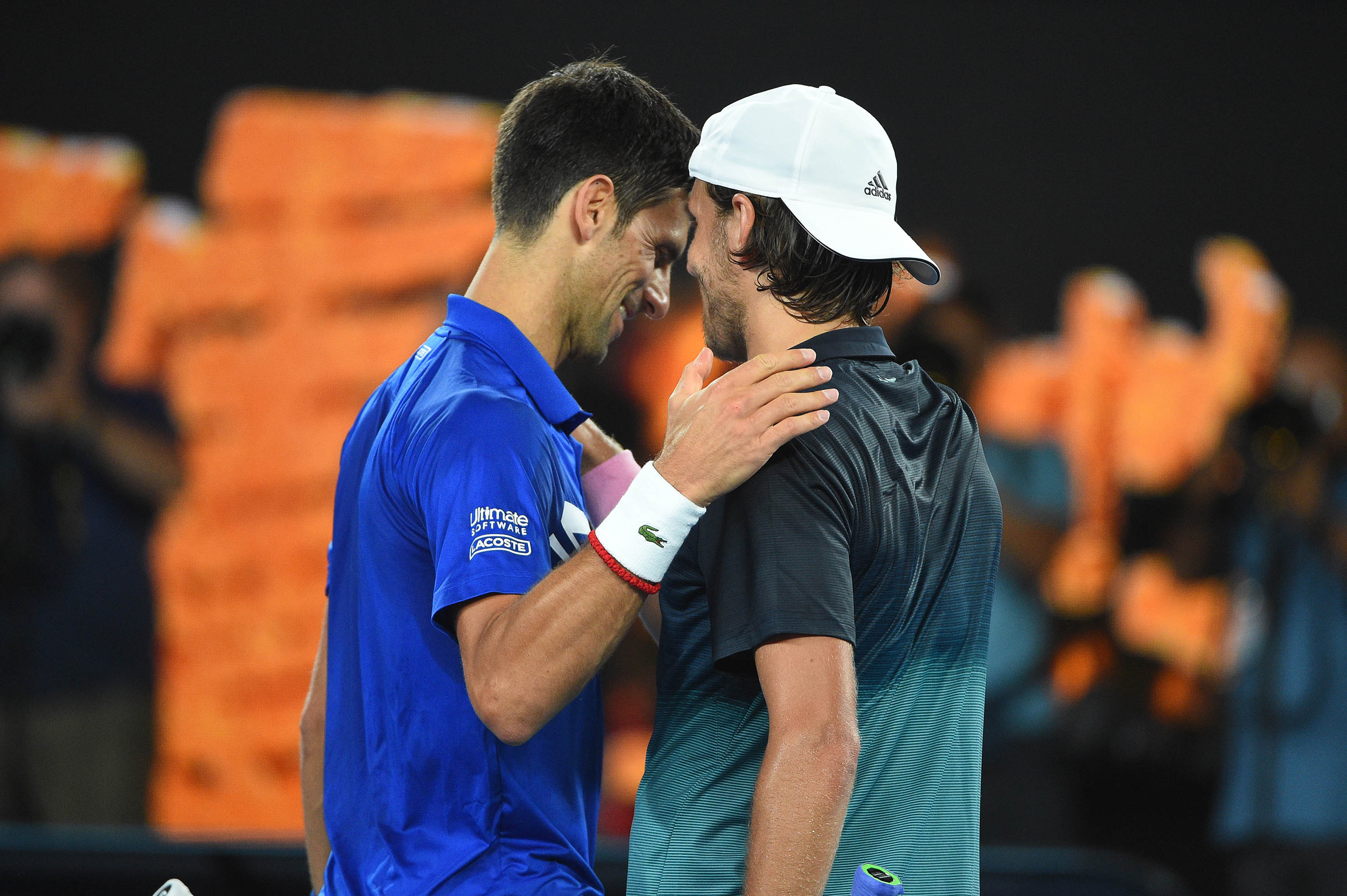 Novak Djokovic and Lucas Pouille at the net during 2019 Australian Open
