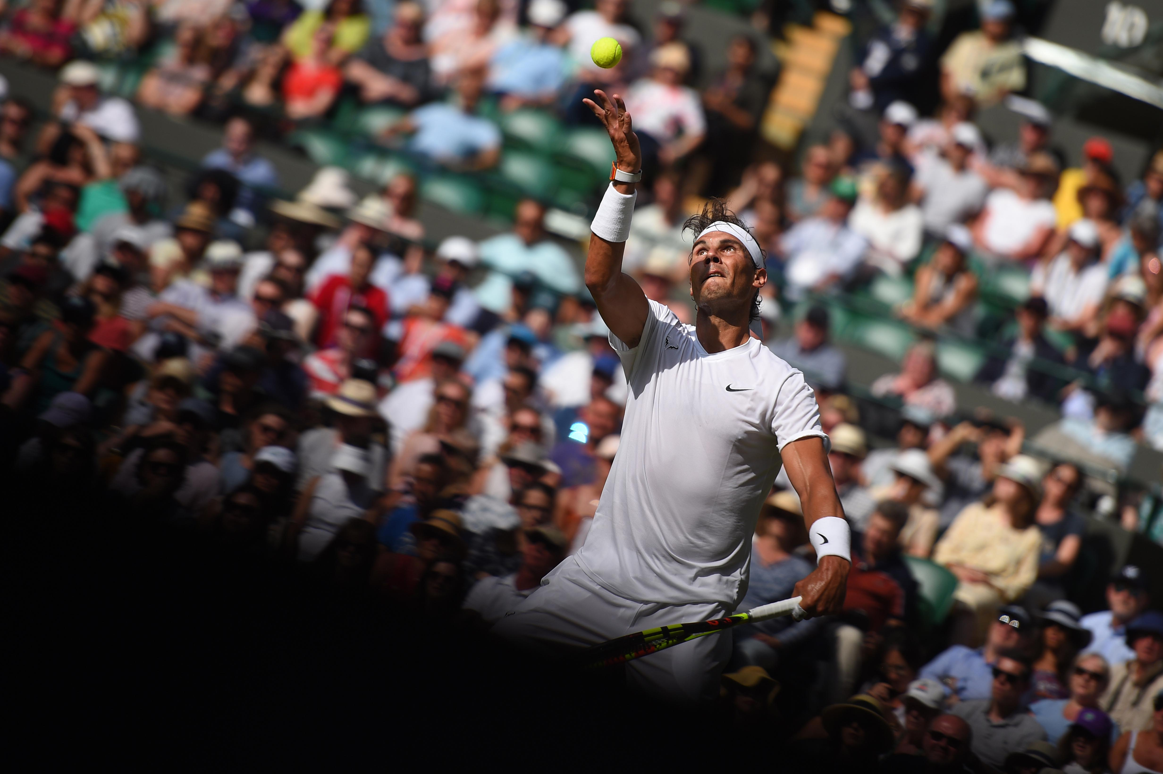 Rafael Nadal serving half in the light, half in the shadow Wimbledon 2019
