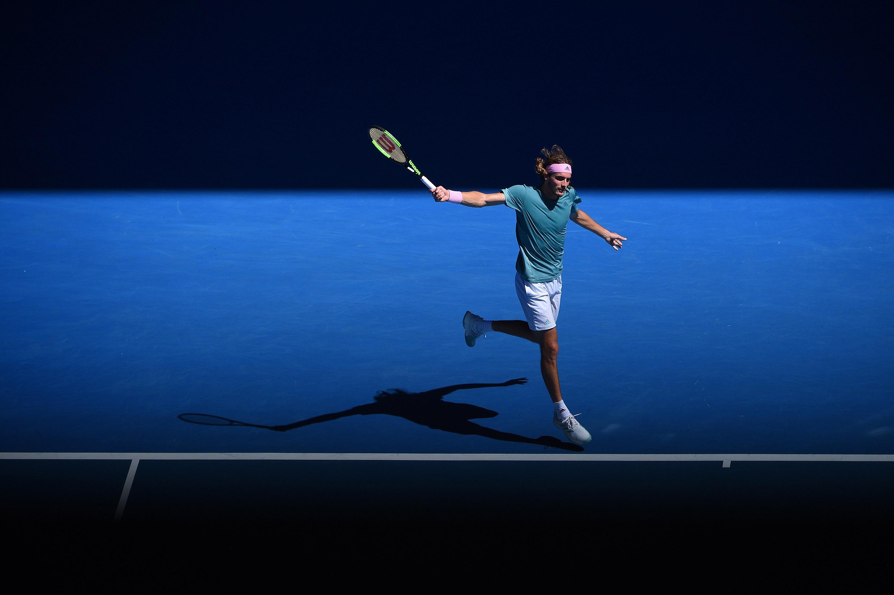 Stefanos Tsitsipas hitting a backhand in the beautiful light of the 2019 Australian Open