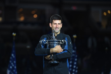 Novak Djokovic smiling while holding the trophy US Open 2018