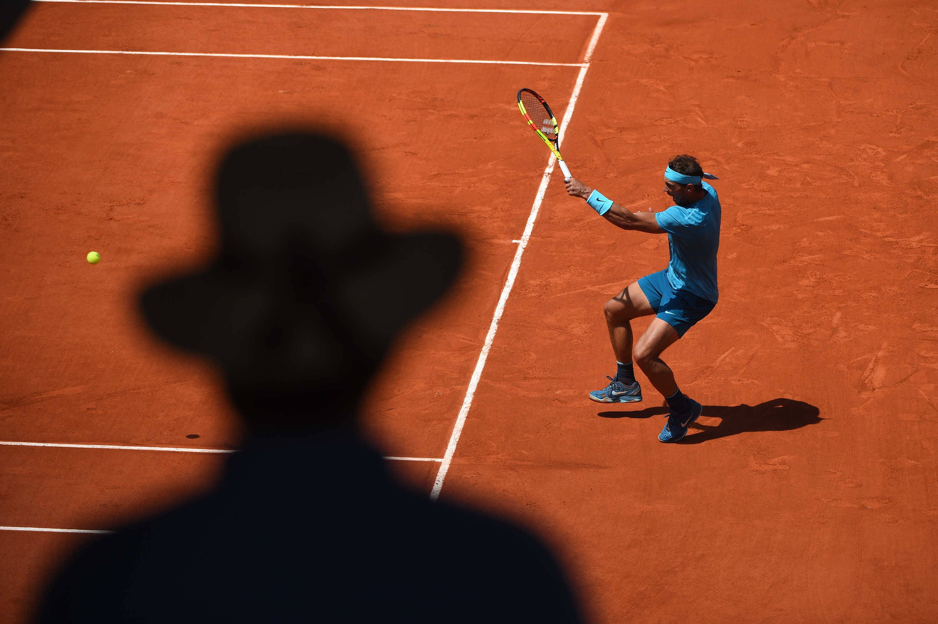 Rafael Nadal hitting a forehand at Roland-Garros 2018 in front of a shadow.