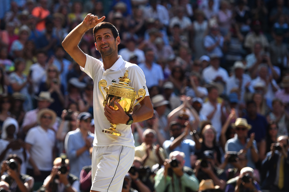 Novak Djokovic smiling as he notices someone in the crowd at Wimbledon 2018